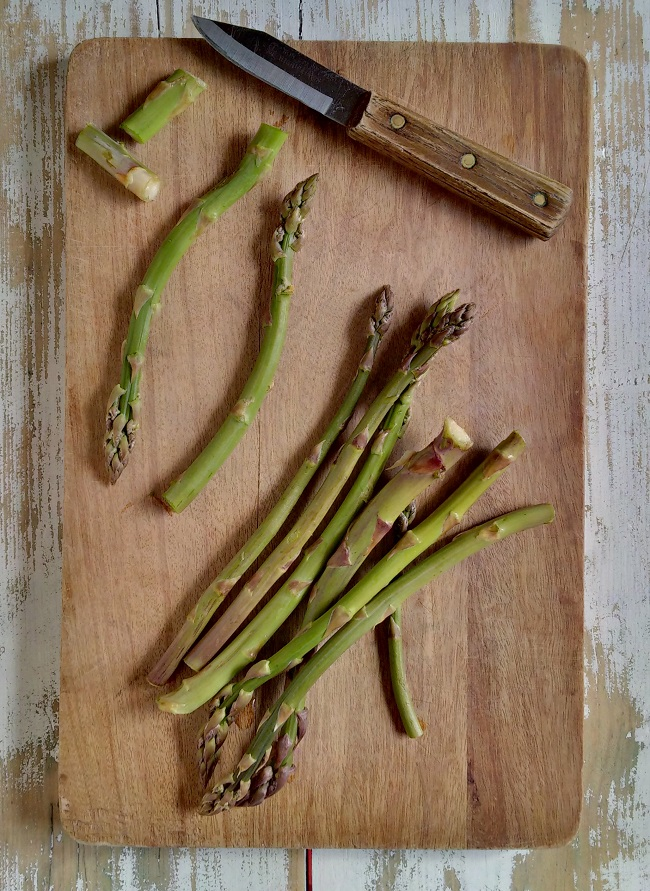 Trimming_away_the_woody_end_from_fresh_asparagus_stems