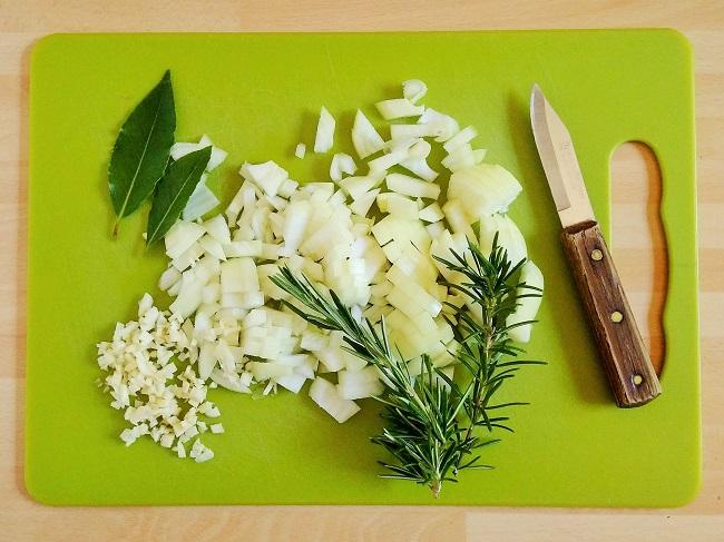 Chopping_board_with_fresh_onion_garlic_bay_and_rosemary