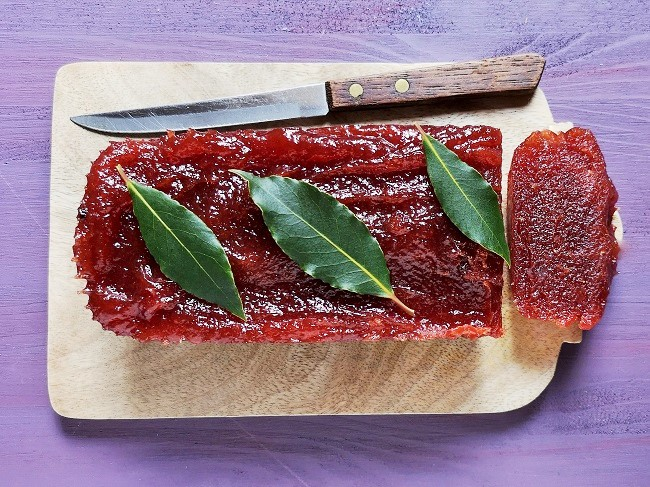 Plum_membrillo_garnished_with_fresh_bay_leaves_being_sliced