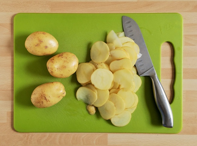 Thinly_slicing_Charlotte_potatoes_for_pilau_cake