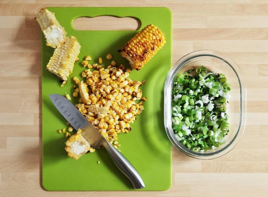 Slicing_off_cooked_sweetcorn_kernels_from_the_cobs