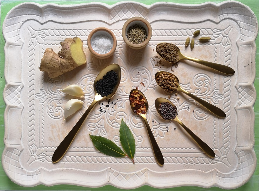 An_array_of_whole_spices_and_seasonings_on_a_wooden_tra_ready_to_flavour_mango_chutney
