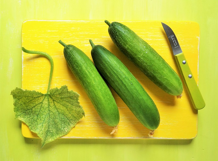 3_mini_cucumbers_with_leaf_on_yellow_chopping_board