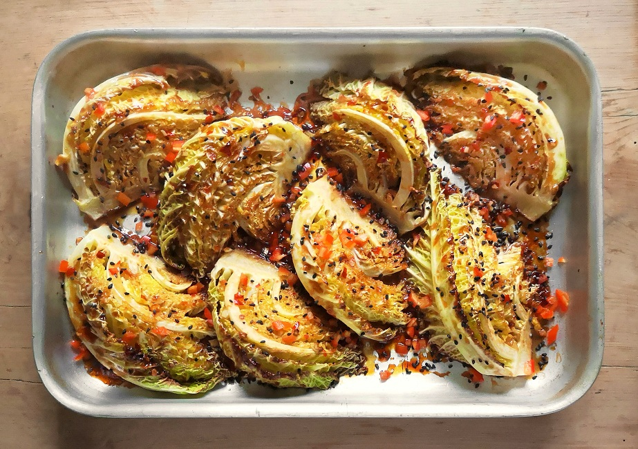 Roasting_tray_of_baked_Savoy_cabbage_wedges_sprinkled_with_chopped_chilli_and_black_sesame_seeds