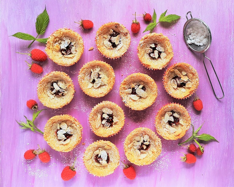 Overhead_image_of_raspberry_and_almond_shorties_with_fresh_berries_and_leaves